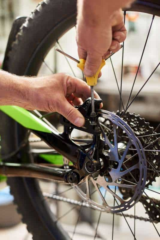 Cropped shot of male mechanic working in bicycle repair shop, installing brakes using special tool