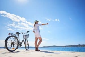 Woman riding a bicycle along stony sidewalk on blue sparkling sea water