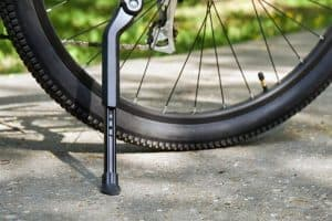 Bicycle kickstand with rear bicycle wheel standing on the asphalt with green grass on the background