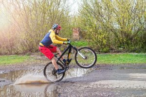 A cyclist in red shorts and a yellow jacket riding a bicycle on the rear wheel through a puddle.